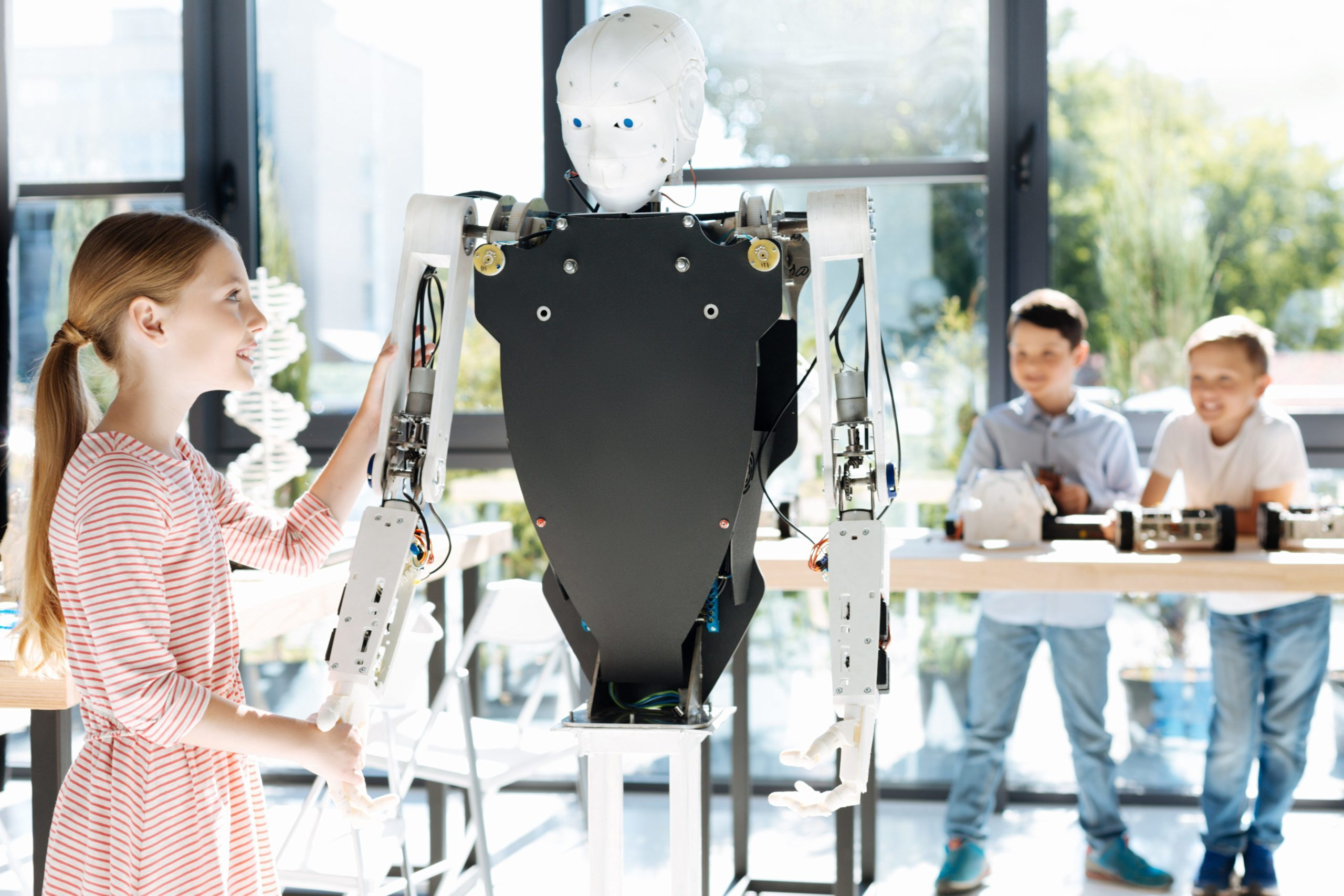 Technological achievement. Beautiful fair-haired pre-teen girl standing near a human robot, shaking its hand as if checking its flexibility while her friends looking at her in the background